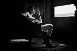 Uncle Charlie contemplating in his living room the reality that his son Joe is dying from HIV, sitting by the window holding his newest and latest handgun in his apartment in Bushwick, Brooklyn in 1996. Image courtesy UArts.